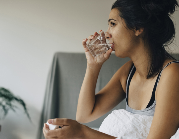 Woman taking pill and drinking water